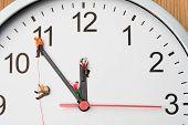 Miniature People Climbing A Clock