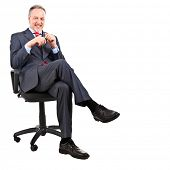 Elder businessman sitting on a chair, isolated on white