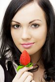 Picture of a beautiful girl, sexy brunette, who eats strawberries