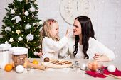 Portrait Of Happy Woman And Her Daughter Cooking Christmas Cookies In Kitchen With Christmas Tree poster
