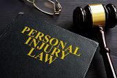 Personal Injury Law Book And A Black Desk. poster