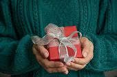 Female Hand Holding Christmas Red Giftbox With Silver Ribbon. Holiday. Boxing Day. poster