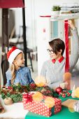 Little girl and her mother preparing red ribbon for tying up giftboxes with xmas presents poster