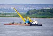 A Pusher With A Barge Is Loaded With Sand, A Floating Crane On The Volga River. Volgograd. poster