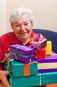 Senior Sits And Gets Or Give Many Gifts