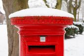 stock photo of postbox  - Traditional English red postbox covered with snow - JPG