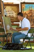Artist Works On Painting At Outdoor Festival