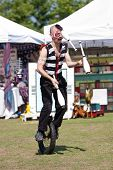 Circus Performer Juggles While Riding Unicycle