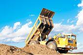 Heavy dump truck unloads soil