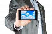 Businessman holds smart phone with cloud computing concept