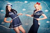 stock photo of tease  - Cute retro portrait of two beautiful navy pinup girls wearing sailor uniforms pulling on a tug of war rope when personal training for elite fitness - JPG