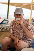 Senior Man Enjoying Drinking Beer On Beach