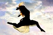 stock photo of leaping  - A young attractive woman leaps through the air with a beautiful cloudy sunset in the background - JPG