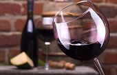 picture of merlot  - Glass of wine and some fruits bottle of wine cheese against a brick wall - JPG
