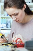 Girl student soldering in the laboratory of electronics