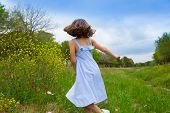 happy children girl jumping on spring poppy flowers meadow with motion blur