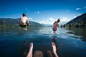children jumping into lake