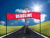 Young businessman running on a road with a banner with deadline written on it