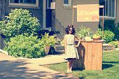 stock photo of yard sale  - retro girl wearing sunglasses with lemonade stand in her front yard - JPG