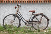old, rusty bike leaning on Wall