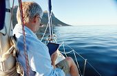 image of sailing vessel  - sailing man reading tablet computer on boat with modern technology and carefree retired senior successful lifestyle - JPG