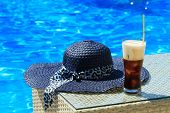 image of frappe  - Ice coffee Fredo against blue clear water of the swimming pool with straw hat - JPG