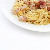 Spaghetti carbonara with fried bacon on white background