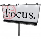 A large white billboard with the word Focus and a target reticle to illusstrate the importance of focusing, aiming or concentrating on your goal or mission in life, work, education or career