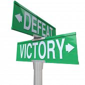 The words Victory and Defeat on two way street or road signs to illustrate the choice between winnin