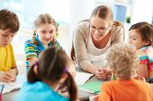 stock photo of diligent  - Portrait of diligent schoolkids and their teacher talking at lesson - JPG