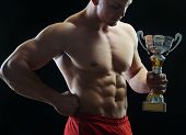 Bodybuilder posing with trophy cup as a winner