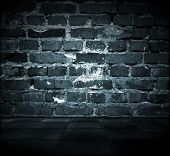 foto of monochromatic  - A dark grungy room with a cracked brick wall and tiled floor - JPG