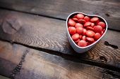 picture of corazon  - Red small candies in heart shaped box against wooden background - JPG