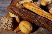 picture of baguette  - Heap of Various Various Buns Baguette Poppy Seed and Sesame Buns Rye and Whole Wheat Bread isolated on Hardwood background - JPG