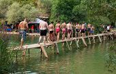 KRAVICE WATERFALLS, BOSNIA AND HERZEGOVINA - AUG 10, 2012: Tourists crossing wooden bridge at Kravice Waterfalls in BH. It is frequently visited by tourists from Medjugorje and Mostar.