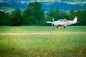 small sport prop aircraft landing on aspahlt runway in green landscape