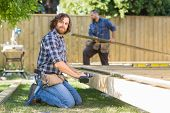 Portrait of confident mid adult manual worker drilling wood with coworker working in background at c