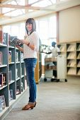 Full length portrait of beautiful college student holding book in bookstore