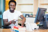 pic of librarian  - Portrait of happy male librarian scanning books at desk in library - JPG