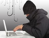 Hacker Working  With A Laptop Computer And Hooks