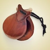 picture of a pair of castanets on a beige background, with a retro effect