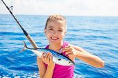 Kid girl fishing tuna little tunny happy with trolling fish catch on boat deck
