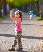stock photo of say goodbye  - little kid with hobo stick bag and bundle girl saying goodbye with hand - JPG