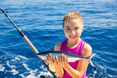 kid girl fishing tuna bonito sarda fish happy with trolling catch on boat deck