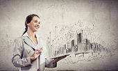 Image of young businesswoman holding ipad against sketch background