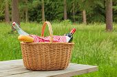 A whicker picnic basket full of food and drink on a table in a woodland setting on a bright summers