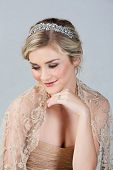 Beautiful blond bride wearing gold dress and diamond tiara as well as a solitare wedding ring on stu