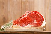 stock photo of t-bone steak  - raw beef Rib steak with bone on wooden board and table - JPG