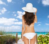 summer holidays, vacation and lingerie concept - back view of beautiful woman in white bikini and ha