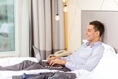 business, technology, internet and hotel concept - happy businessman with laptop computer lying in hotel in bed